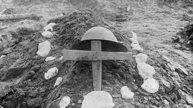 A helmet hangs on a makeshift wooden cross on the dirt grave of an unknown Canadian soldier, World War I.