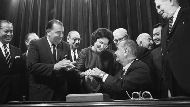 President Johnson hands a pen to the first lady after signing her highway beautification bill into law in a ceremony at the White House.