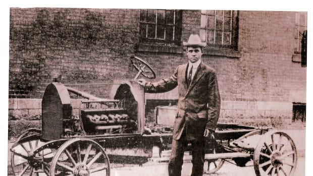 Frederick Patterson standing beside a bare Patterson-Greenfield automobile chassis, probably for a larger touring car body.