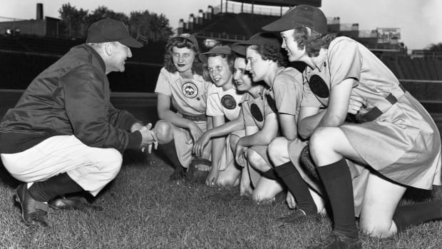 Members of the All-American Girl's Professional Baseball League's Rockford Peaches gather with their coach, Eddie Stumpf, during practice in May 1944.