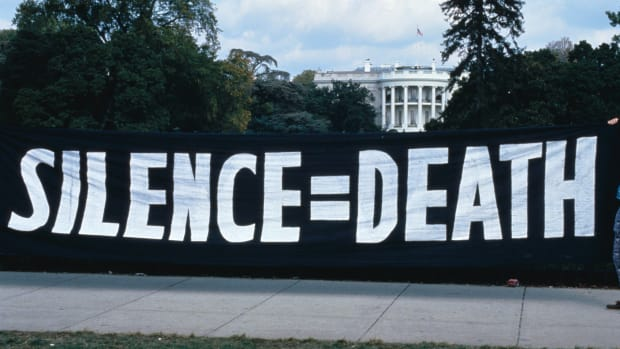 """ACT UP activists hang a """"silence = death"""" banner on the White House gates in 1992."""