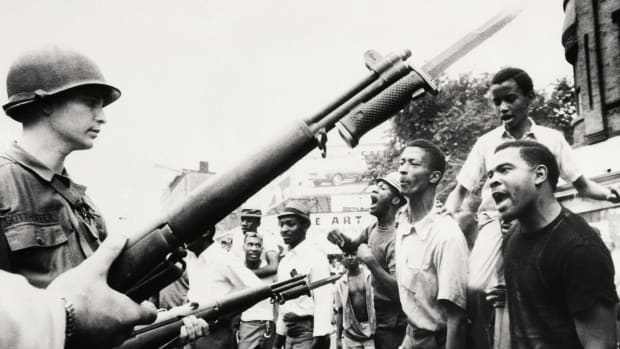 Newark, New Jersey, July 14, 1967: Negroes jeer at bayonet-wielding National Guardsmen here July 14th. The National Guard and New Jersey state police were called out July 14th to aid Newark police, following the second night of disorder in this, New Jersey's largest city.