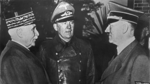 French Marshal and Vichy leader Henri-Philippe Petain (1856 - 1951, left) and Nazi leader Adolf Hitler (1889 - 1945, right) share the famous 'handshake at Montoire' while interpreter Colonel Schmidt watches, October 1940. Thus Petain announces officially that Vichy-France is prepared to collaborate with the German Reich.