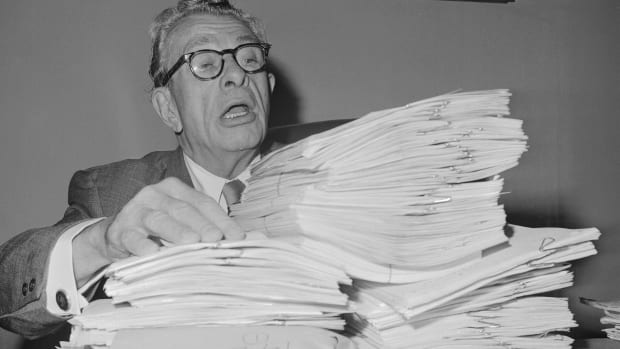 """Senate GOP leader Everett M. Dirksen stacks up some of the reading material October 4, 1965, that will use in his planned filibuster against a bill to nullify state """"right to work"""" laws."""