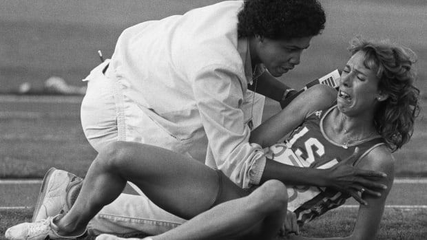 Mary Decker of the USA, comforted by a track official, cries out in frustration after falling down during the women's 3000m final at the Olympic games 11 August 1984 in Los Angeles (B&W only). AFP PHOTO JEAN-CLAUDE DELMAS