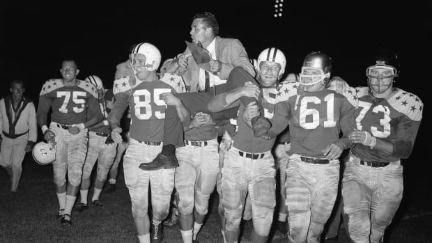 (Original Caption) Otto Graham, head coach of the College All-Stars, is carried from the field by victorious All Stars after 35-19 win over the Detroit Lions in the 25th annual All-Star game in Soldiers Filed here 8/15. Left to right: Wayne Walker, #75, Idaho; Bob Jewett, #85, Michigan State; Tony Stremic, #61, Navy and Charles Howley, #73, West Virginia.