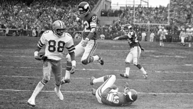 """In this Dec. 28, 1975, file photo, Dallas Cowboy wide receiver Drew Pearson (88) nears the end zone on a game-winning 50-yard touchdown pass play in the fourth quarter of an NFL football game against the Minnesota Vikings in Bloomington, Minn. Cowboys quarterback Roger Staubach explained his game-winning throw by saying, """"I closed my eyes and said a Hail Mary. Staubach and Pearson have connected again as part of a project to create a digital collectible of their famous Hail Mary for the Dallas Cowboys against Minnesota in 1975. It's part of an emerging product in sports memorabilia called non-fungible tokens, or NFTs. (AP Photo/File)"""