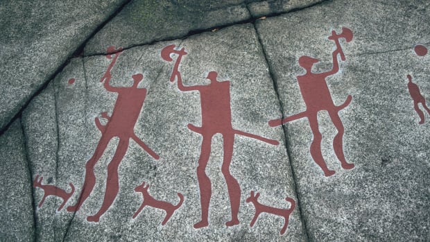 A prehistoric petroglyph at a Bronze Age site in Tanum, Bohuslan, Sweden, depicting three figures wielding axes.