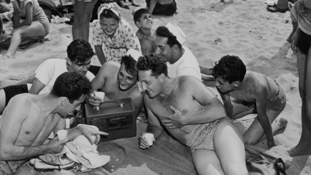 A group of young people listening to a portable radio on the beach at Coney Island, New York, July 1947