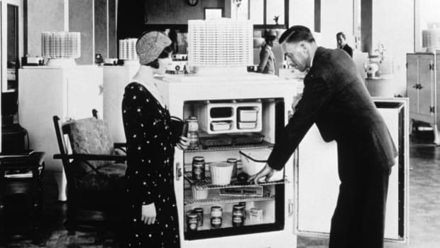 Salesman demonstrating an electric refrigerator to a shopper, c. 1920
