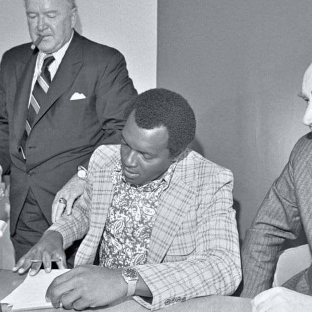 With Oakland A's owner Charles Finley at his side, pitcher Vida Blue signs a contract