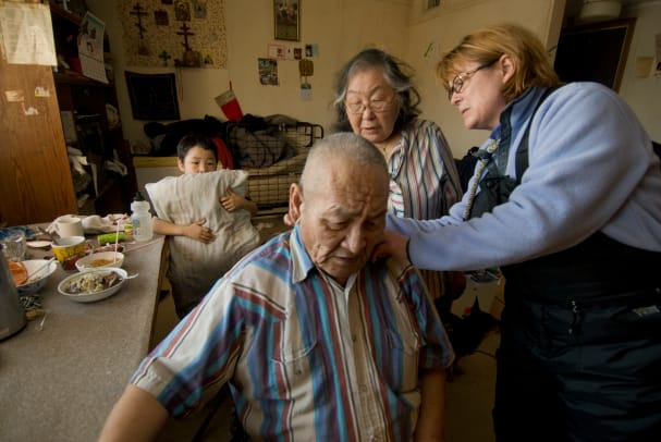 Alaskan Public Health Nurse Visiting Elderly Man At Home