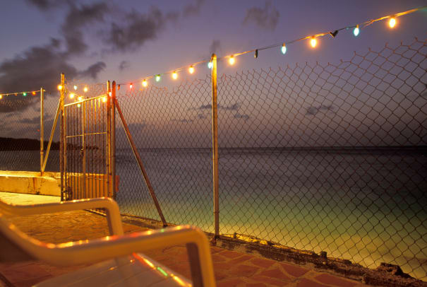 Fence Decorated With Christmas Lights Beside The Sea