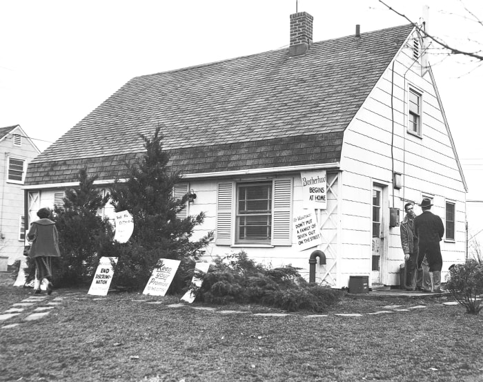 A house sublet by William Cotter and his family was paneled in the front yard in a last ditch effort to prevent the family's eviction in Levittown, New York, 1953. The Cotters were the first black family to move out. in the subdivision and were denied having renewed his lease or bought his house;  the family filed a complaint of racial discrimination.