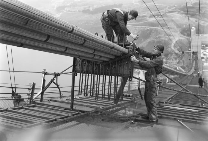 Workers on the catwalks bundling the cables during the construction of the cables of the Golden Gate Bridge in San Francisco, California, c. 1936.