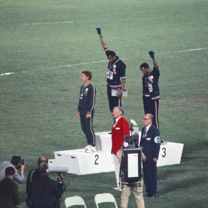 American sprinters Tommie Smith, John Carlos and Peter Norman during the award ceremony of the 200-meter race at the 1968 Olympic games. During the ceremony, Smith and Carlos protested against racial discrimination: they went barefoot on the podium and listened to their anthem bowing their heads and raising a fist with a black glove.