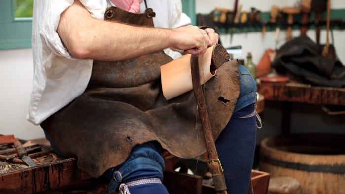 A man reenacts the role of a colonial cobbler in Williamsburg, Virginia.