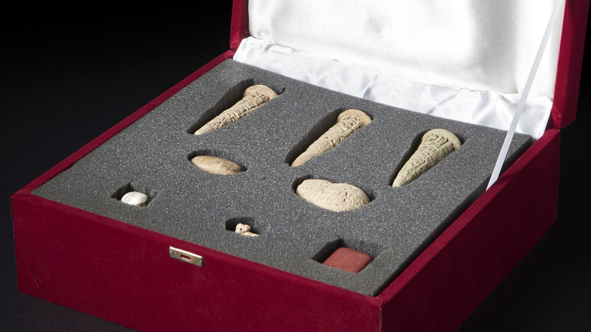 The artifacts consisted of three complete fired clay cones, a mace-head, river pebble with an Old Sumerian inscription, and a red and white marble stamp seal. (Credit: The British Museum)