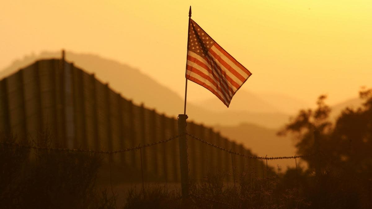 A U.S. flag, put up by activists who oppose illegal immigration, near the US-Mexico border fence in an area where they search for border crossers near Campo, California, 2006. (Credit: David McNew/Getty Images)