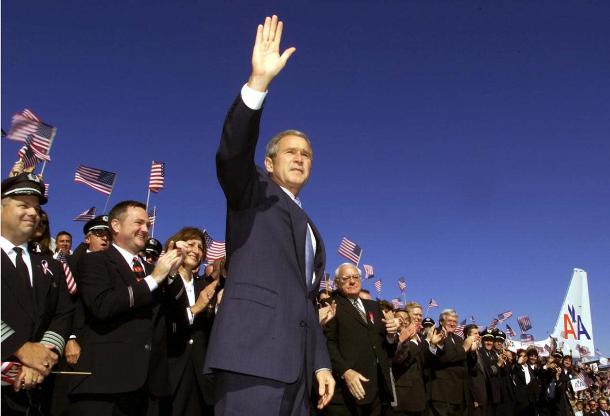 US President George W. Bush waving to thousands of airline employees before his speech to announce expanded US aviation security procedures which include more Air Marshals, aircraft cockpit modifications and new standards for ground security operations at Chicago's O'Hare International Airport. (Credit: Paul J. Richards/AFP/Getty Images)