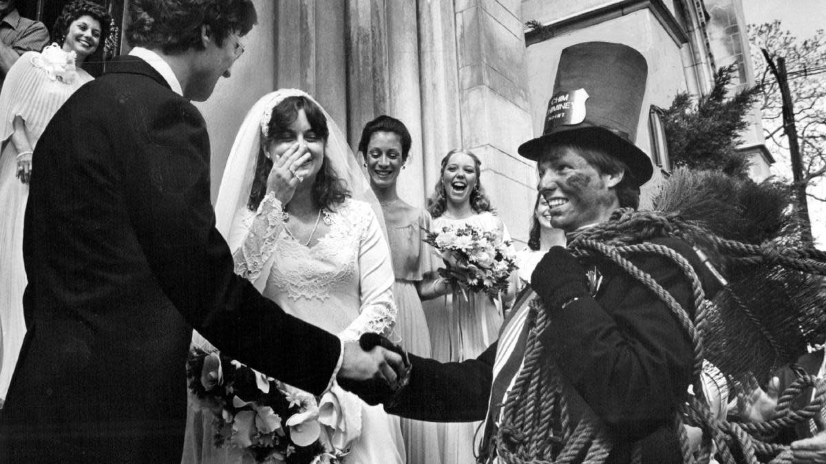 Newlyweds keeping alive a centuries-old tradition of having a chimney sweep wait outside a church and shake hands with wishes of good luck. (Credit: Ernie Leyba/The Denver Post via Getty Images)