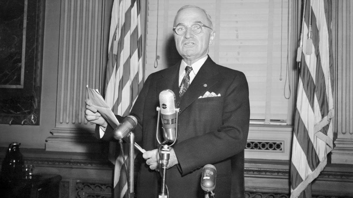 Following a press conference, President Harry S. Truman poses for photographers reading the statement in which he grimly warned Communist aggressors that the U. S. is considering using the atomic bomb in the Korean War. (Credit: Bettmann Archive/Getty Images)