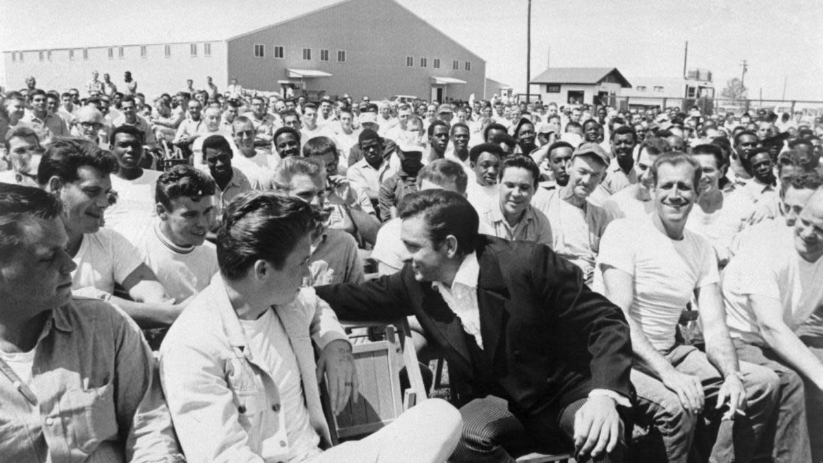 Johnny Cash chatting with some of the inmates and guests during his visit to Cummins Prison in Arkansas. April 10, 1969. (Credit: Bettmann Archive/Getty Images)