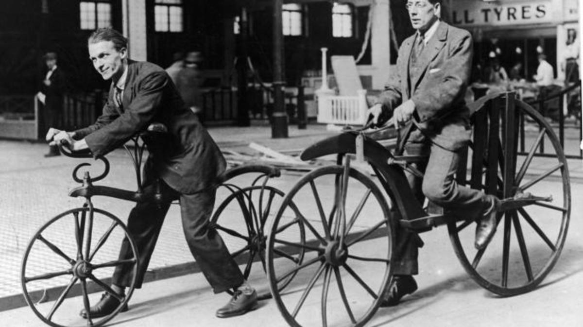 Two men ride on early bicycles known as the Hobby Horse and 'Boneshaker'. The Hobby Horse was invented by Karl Von Drais in 1818 and was operated by kicking against the street. By 1863, cranks and pedals were added to to create the 'boneshaker'. (Credit: Herz/Getty Images)