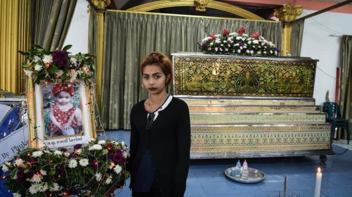 Jiranuch Trirat, 22, stands in front of the coffin of her slain 11-month-old daughter Natalie at a temple in Phuket on April 27, 2017. (Credit: LILLIAN SUWANRUMPHA/AFP/Getty Images)