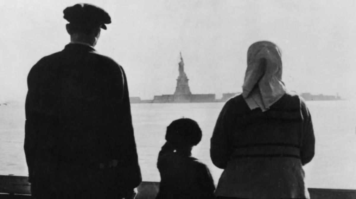 An immigrant family on Ellis Island looking across New York Harbor at the Statue of Liberty, 1930s. (Credit: FPG/Getty Images)