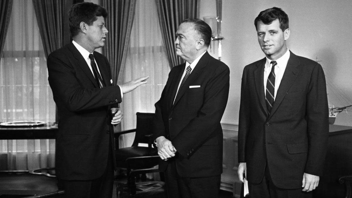 FBI Director J. Edgar Hoover, accompanied by Attorney General Robert Kennedy, chatting with President John F. Kennedy. (Credit: Bettmann Archive/Getty Images)