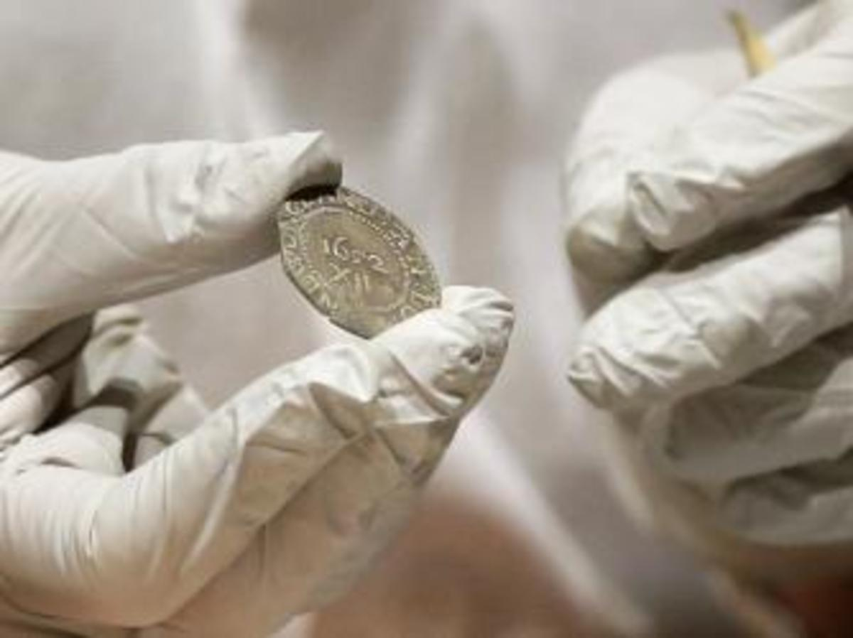 """Hatchfield holding the 1652 """"Pine Tree Shilling"""" found in the capsule (Credit: Bostom Museum of Fine Arts)"""