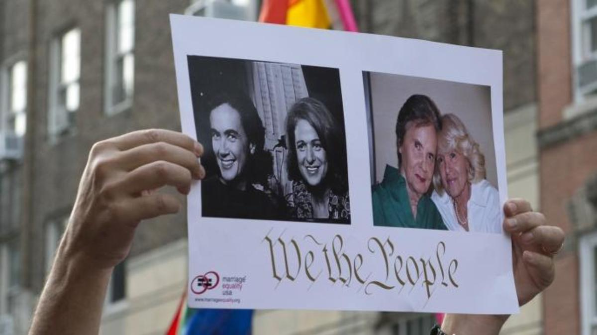 A poster of Edie Windsor, plaintiff in United States v. Windsor case, and her partner Thea Spyer, is held above a crowd gathered outside Stonewall to celebrate the Supreme Court ruling on the Defense of Marriage Act. (Credit: Don Emmert/AFP/Getty Images)
