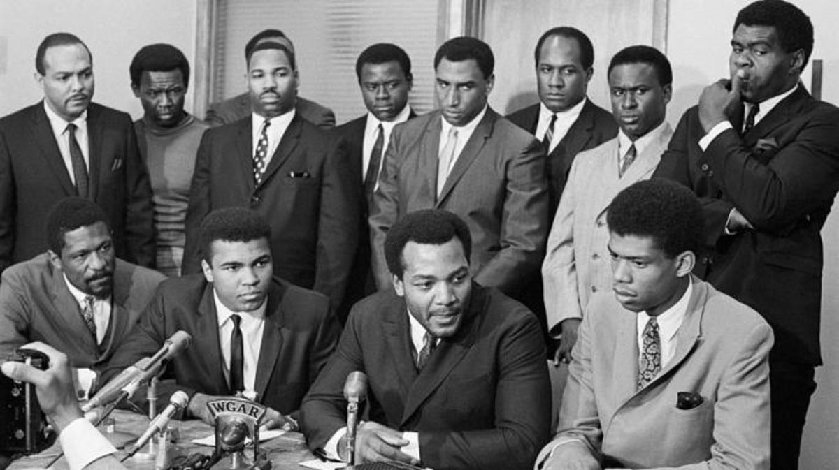 African American athletes and politicians at a press conference in support of Ali's decision. Front row: Bill Russell, Ali, Jim Brown and Kareem Abdul-Jabbar (then known as Lew Alcindor). Back row: Carl Stokes, Walter Beach, Bobby Mitchell, Sid Williams, Curtis McClinton, Willie Davis, Jim Shorter and John Wooten.