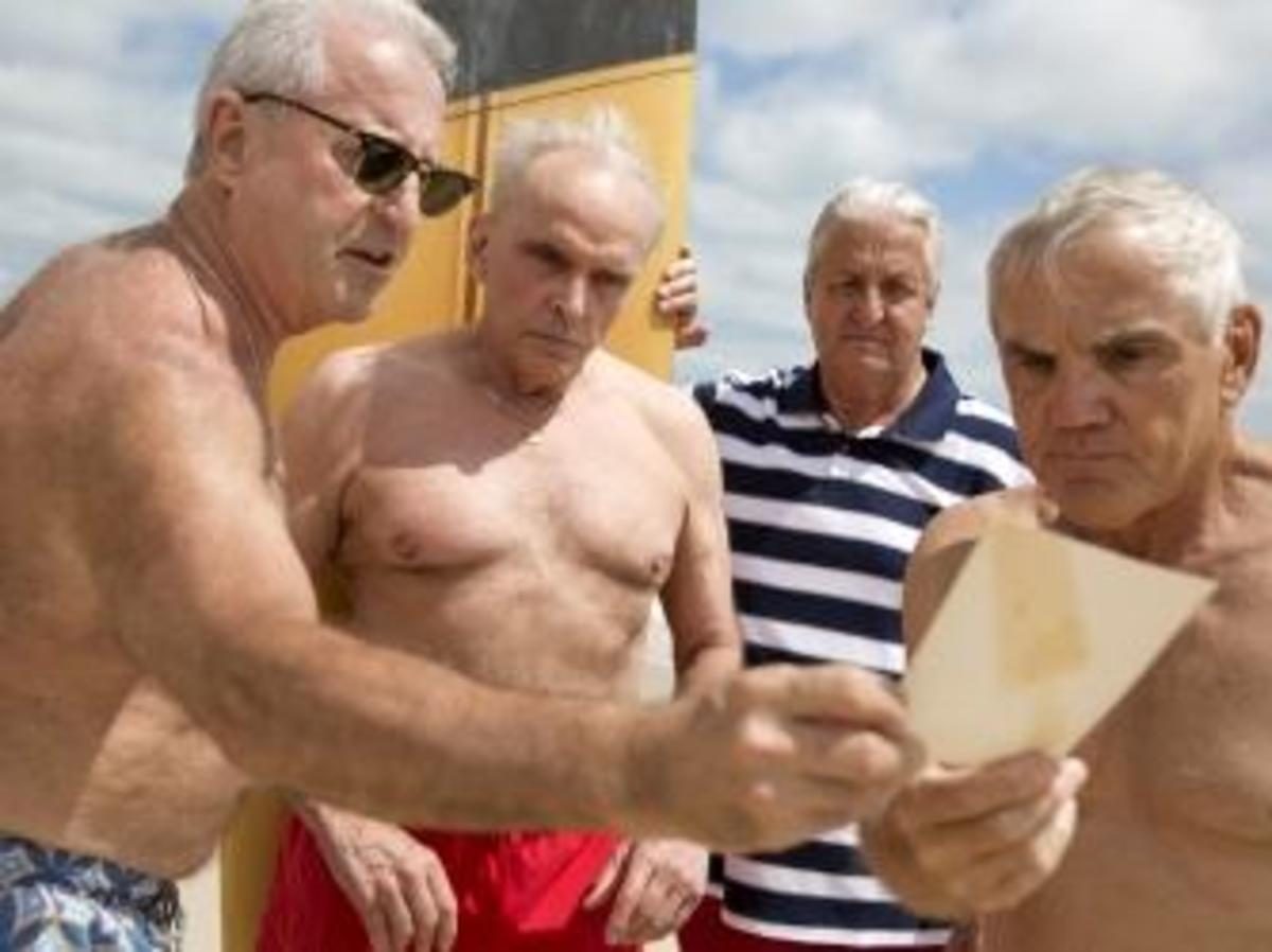 From the left, Dennis Puleo,Tom Hanks, Bob Falk, and Bob DeVenezia view the photograph, taken nearly 50 years, they are recreating. (Credit: Naples Daily News)