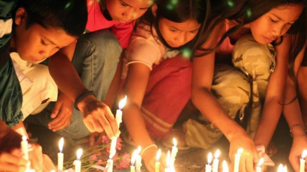 Filipino children light candles for slain Peace Corps volunteer Julia Campbell in Legaspi, Philippines, in May 2007