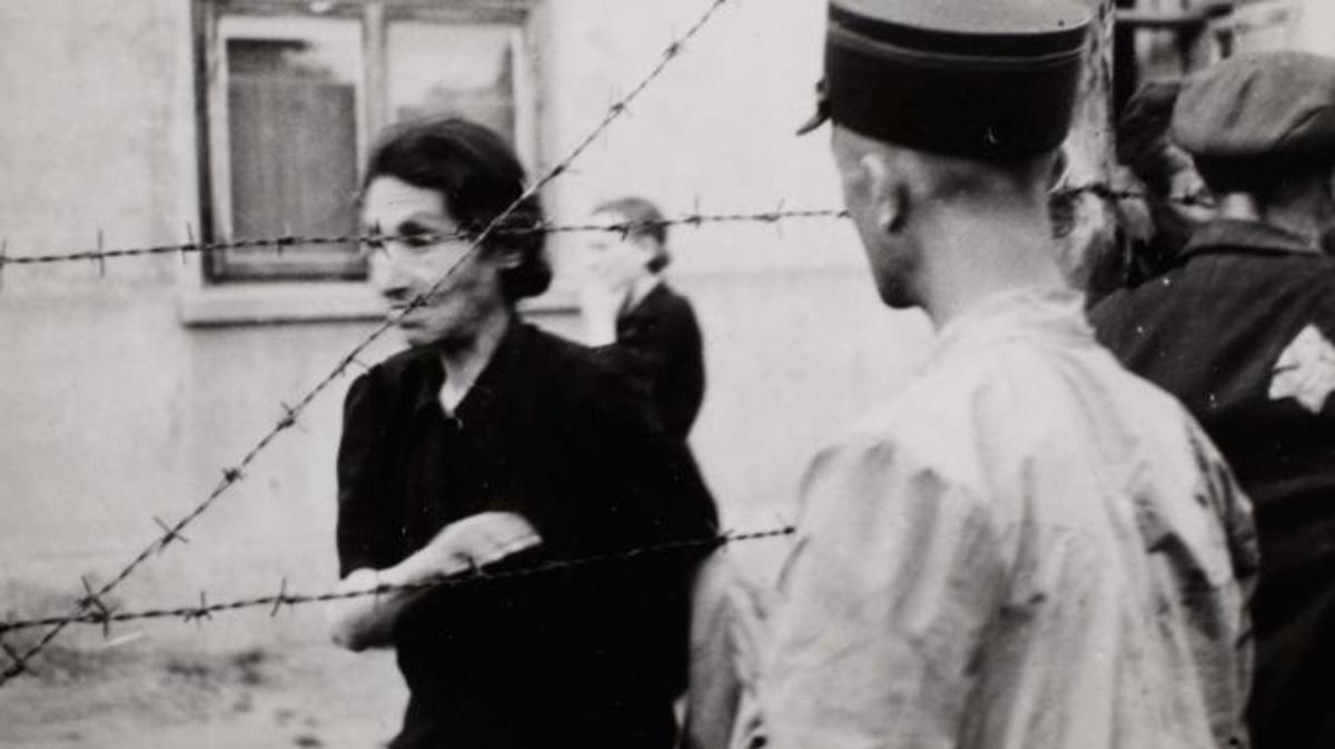 Ghetto police with woman behind barbed wire, 1940-1944, by Henryk Ross.