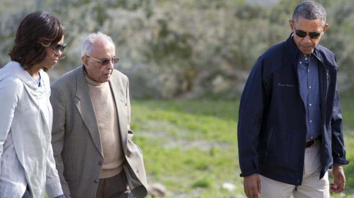 US President Barack Obama and First Lady Michelle Obama listen to former prisoner Ahmed Kathrada as they tour the limestone quarry where prisoners worked on Robben Island. (Credit: SAUL LOEB/AFP/Getty Images)