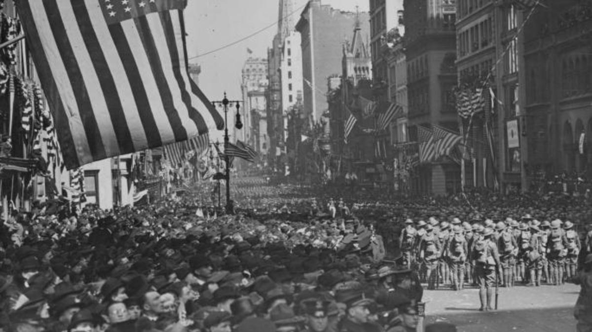 A military parade with crowds of excited spectators along 5th Avenue, in celebration of Armistice day and peace in Europe following World War One, New York, 1918. (Photo by Paul Thompson/FPG/Getty Images)