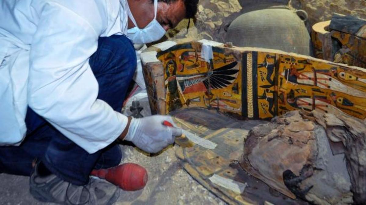 A member of an Egyptian archaeological team works on a wooden coffin discovered in a 3,500-year-old tomb in the Draa Abul Nagaa necropolis. (Credit: STRINGER/AFP/Getty Images)