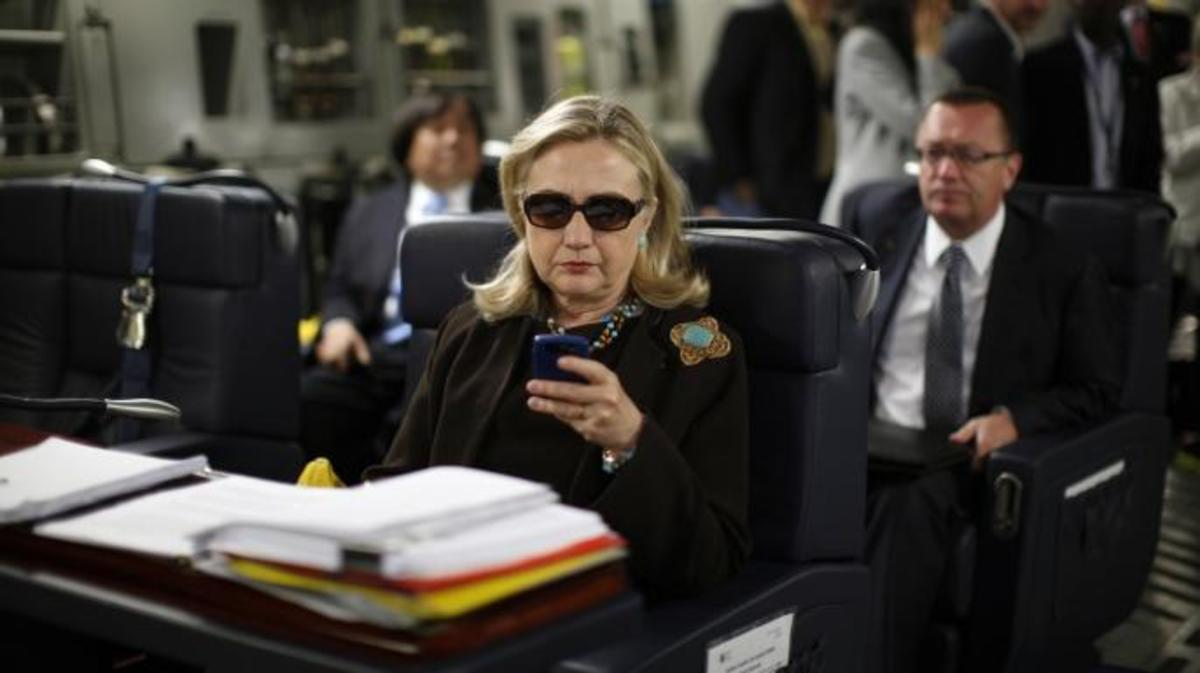 Then-Secretary of State Hillary Rodham Clinton checks her Blackberry from a desk inside a C-17 military plane upon her departure from Malta, in the Mediterranean Sea, bound for Tripoli, Libya. (Credit: AP Photo/Kevin Lamarque, Pool, File)