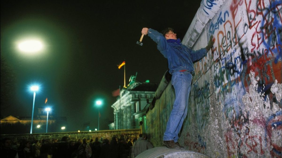 January 1, 1990: A German citizen takes a hammer to the Berlin Wall, one of the most potent symbols of the Cold War. (Photo by Guy DURAND/Gamma-Rapho via Getty Images)