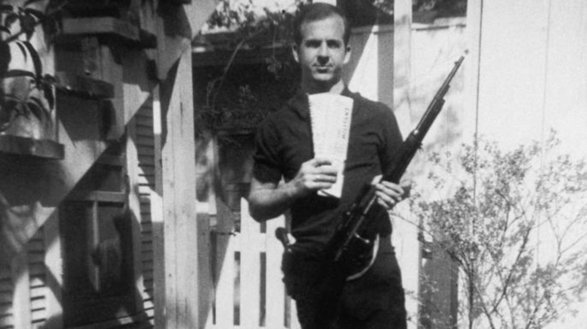 Lee Harvey Oswald holds a Mannlicher-Carcano rifle and newspapers in a backyard. This is one of the controversial photos used in the investigation of the assassination of John F. Kennedy in 1963. (Credit: Corbis via Getty Images)