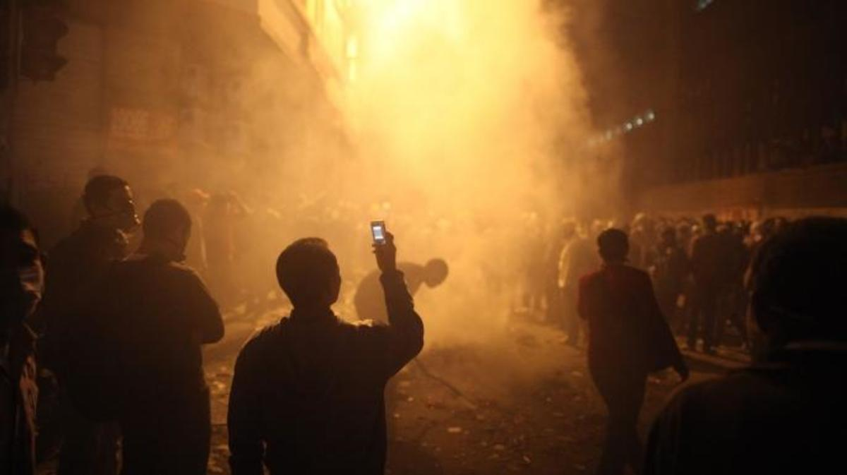 A youth films the aftermath of a tear gas volley fired by police on protestors in Muhammed Mahmoud Street near Tahrir Square on November 23, 2011 in Cairo, Egypt. (Credit: Peter Macdiarmid/Getty Images)
