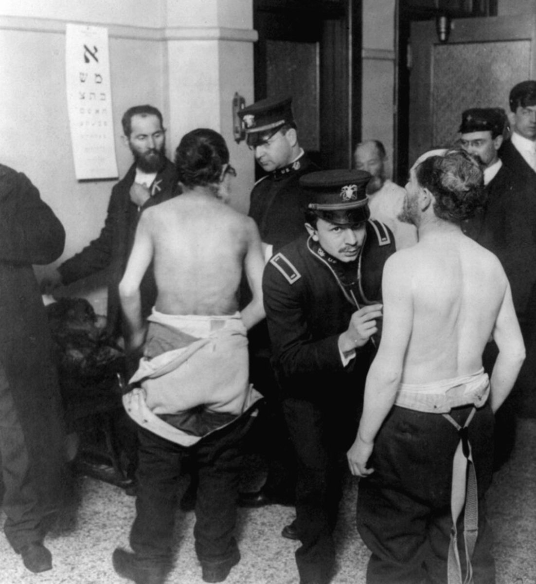 Physicians examining a group of Jewish immigrants who are gathered in a small room on Ellis Island. (Credit: Universal History Archive/UIG/Getty images)
