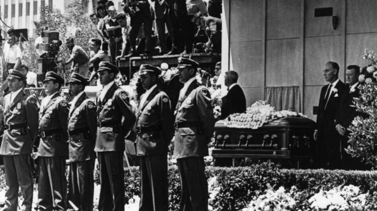 Detectives from the Pinkerton Agency guard the coffin of  Marilyn Monroe at her funeral in Westwood Memorial Park, in August 1962.  (Credit: Keystone/Getty Images)