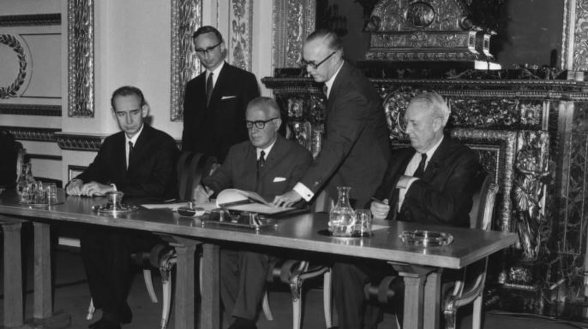 Britain's Foreign Secretary Michael Stewart signs the treaty on the Non-Proliferation of Nuclear Weapons at Lancaster House, London, watched by the Soviet Ambassador (L) and the US Ambassador (R), July 1 1968.  (Credit: Jim Gray/Keystone/Getty Images)