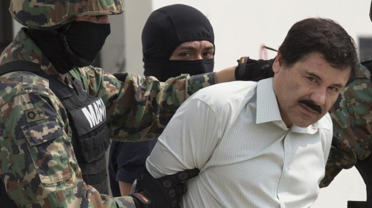 """Drug trafficker Joaquin """"El Chapo"""" Guzman is escorted to a helicopter by Mexican security forces. (Credit: Susana Gonzalez/Getty Images)"""