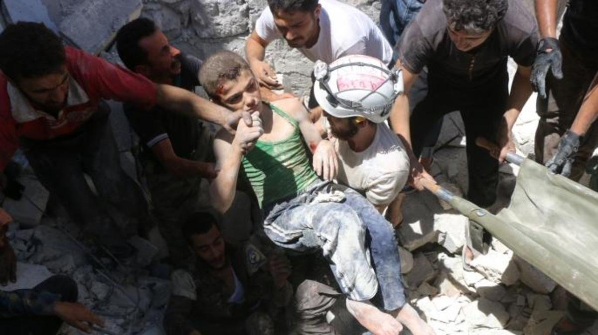 The White Helmets carry a young boy after they dug him out from under the rubble of buildings destroyed following reported air strikes on the rebel-held neighborhood of Al-Mashhad in the northern city of Aleppo, on July 25, 2016. (Credit: THAER MOHAMMED/AFP/Getty Images)