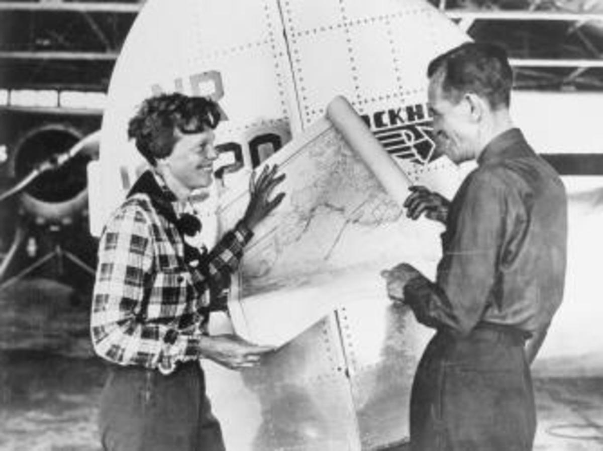 Pilot Amelia Earhart and her navigator, Fred Noonan, with a map of the Pacific that shows the planned route of their last flight. (Credit: Bettmann/Getty Images)